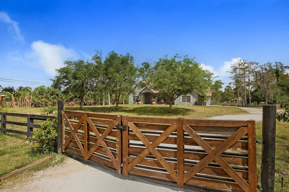 EQUESTRIAN SEASONAL STEAL! Beautiful 5 bed/3.5 bath, fully furnished home for rent this winter in Loxahatchee Groves on 1.73 acres and only 5.8 miles to Winter Equestrian Festival and 1.3 miles to Wellington! You'll love the high ceilings allowing for lots of light, 3 sided fireplace, large covered patio and open pool area for sun bathing. The wooden front gate to the property was made from a 100 yr old barn! Fully fenced yard, 5 camera security system and last house on the street give wonderful privacy. There is also a large pig pen in the side yard and a local polo field on the neighboring property. Flexible move in dates available, prefer at least a 4 month lease.
