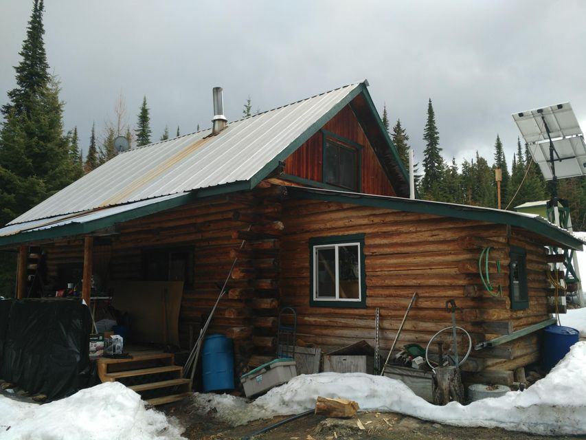 Want your own retreat in the mountains?? Take a look at this off the grid log cabin on almost 20 acres ! Super private and borders forest service on 2 sides ! Comes with it's own little dozer to putter around the place and to plow the driveway. Set up off the grid with a battery bank and a generator and solar panel. Hi speed internet and phone line already installed. Septic system installed and comes with Fantastic mountain views !