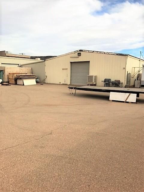 Property zoned industrial.  Corner property has good exposure and access. 2 buildings, main bldg. 4,280 sq ft, roll up doors, includes 1,000 office space.  1,500 sq ft warehouse/shop w/roll up door. .37 acre, fully paved lot for lots of parking. Partially fenced. Call agent to see property. Occupied.