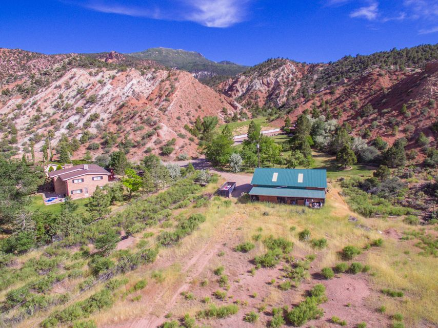 You cannot beat this location! Situated at the base of Cedar Canyon near the canyon park & walking trails & sitting on 2.70 acres of hard to find horse property right near the center of town. This all brick home backs up to cedar mountain making you feel you have escaped to the hills, all the while, being in the City.  This home offers amazing views of Cedar Canyon, 1800 sq ft shop with wood stove