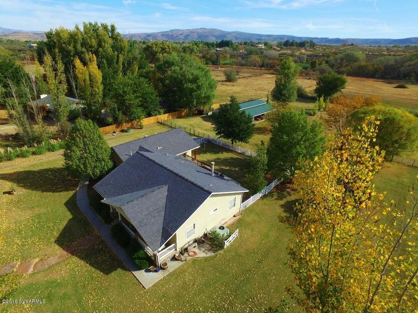 Great main house with 5.14 irrigated acres. great country home with Barn Master brand large hay &  mare motel with a tack and office room which can be added onto or converted to 8 stall barn. House is move in ready, newly cleaned and ready to go. Two sets of French doors to office and Dining Room, spacious kitchen with built in desk area, Great Room with cathedral ceilings, river rock fireplace, access to large deck. Spacious master and master bath with large garden tub, separate large walk in shower, double vanity, oil rubbed bronze lighting. Welcoming guest bedrooms with shared bath. Kitchen is open with drop custom pendant lighting over breakfast bar, bay window 4 burner gas stove and oven, hickory cabinetry. Great country home. Don't miss this one.