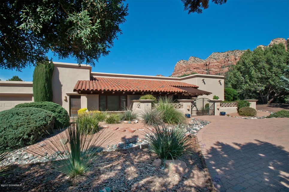 The epitome of Southwest living in Sedona, this is the perfect blend of fantastic red rock views in a gorgeous 1-acre private setting, a gracious modern floorplan, a home that's beautifully updated, and upscale Southwest design touches that merge with the luxurious and flawlessly appointed treatments. This home exudes warmth and character, from the front entry gate and courtyard to the open back patio overlooking a border of trees and unimpeded red rock views, from the bright entry foyer and elegant Gourmet Kitchen, to the delightful Living Room and adjacent spacious Media Room/Study, this single level sophisticated Southwest home is truly a Sedona gem The Kitchen has been completely updated with granite countertops and new cabinetry, Electrolux appliances, large island, walk-in pantry,