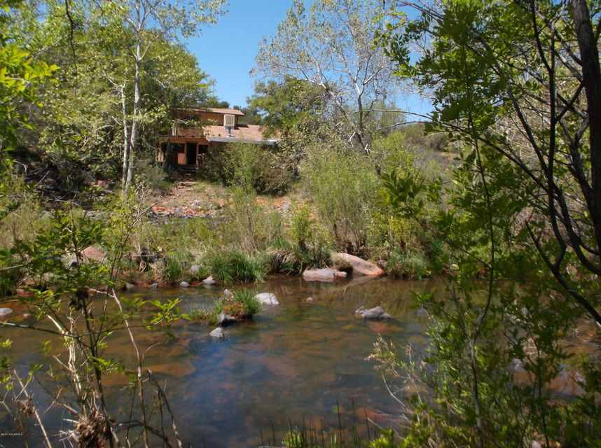 Secluded Oak Creek property on 4.15 acres. Quiet and super private with old home and structures. Not livable  without renovation as may be allowed by Yavapai County Building and Flood Control Depts. However detracting the condition of the structures may be, the sounds of water and the location are rare and irreplaceable. The creek sounds and beautiful trees, impressive volcanic cliff walls will mesmerize. Make you feel relaxed and carefree. Includes potential for ''old'' irrigation rights from irrigation ditch easement that runs through the property. SHOWN BY APPMNT ONLY. SOLD AS-IS. Includes well & septic system and out of flood plain areas to build a new home-shop if you like. *Travelers to property BE WARNED access is by rough and narrow U. S. Forest Service road. Drive SLOW & SAFE