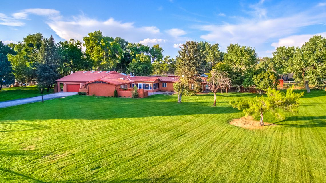 Offers welcome! Mid Century on acreage. Nestled under majestic cottonwoods on 2.45 eastside acres.A recently remodeled 5BR, 5000sf home w/2 car gar, plus a 2BR 600sf casita, 1150 sf workshop w/bath.  Gated entry! New windows, floors, & septic! Well designed for a large family w/high ceilings. Formal living,dining,fabulous kitchen w/ island, granite, SS appliances. Open to FR w/FP. Media room, studio room, great laundry room. MBR suite w/sitting area, walk in closet & workout area! Separate 3BR/Bath wing plus 1BR/bath area. New wood & carpet floors, simply beautiful. Corrales Road access for casita.  Workshop fits several cars! Area for horses! A great property!  Access to the Bosque for trails and open space! Property is in 2 parcels. South end Corrales location. A beautiful property.