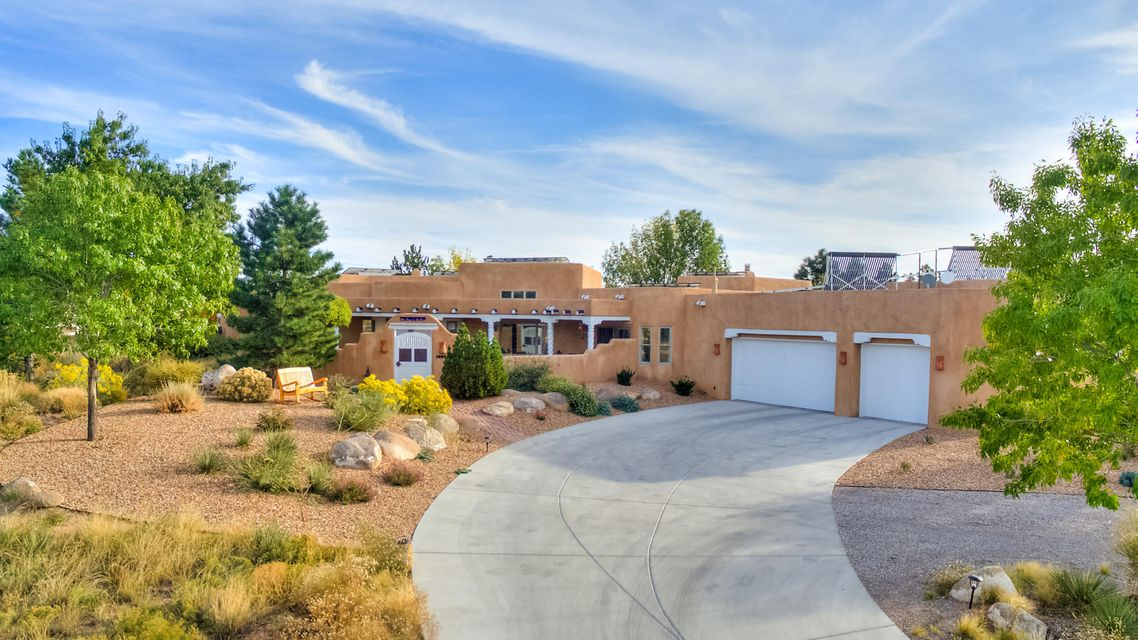 This exceptional home was designed and built by Penny Nafus in her distinctive New Mexican style. You will treasure the architectural details and fine finishes including carved posts, viga and latilla ceilings, custom doors and hardware.  3 masonry kiva fireplaces add warmth and character. The fully updated kitchen is a chef's dream that you MUST see with upscale appliances, plentiful cabinets and counter space. Incredible outdoor living from the grassy courtyard entrance to the covered portal & extended backyard patios with those mountain and sunset views! All bathrooms are updated; walnut wood and saltillo floors.  Mechanical features include newer TPO roof, solar panels, and a 5 CAR heated garage. Lovingly cared for and meticulously updated, this home is truly a masterpiece!