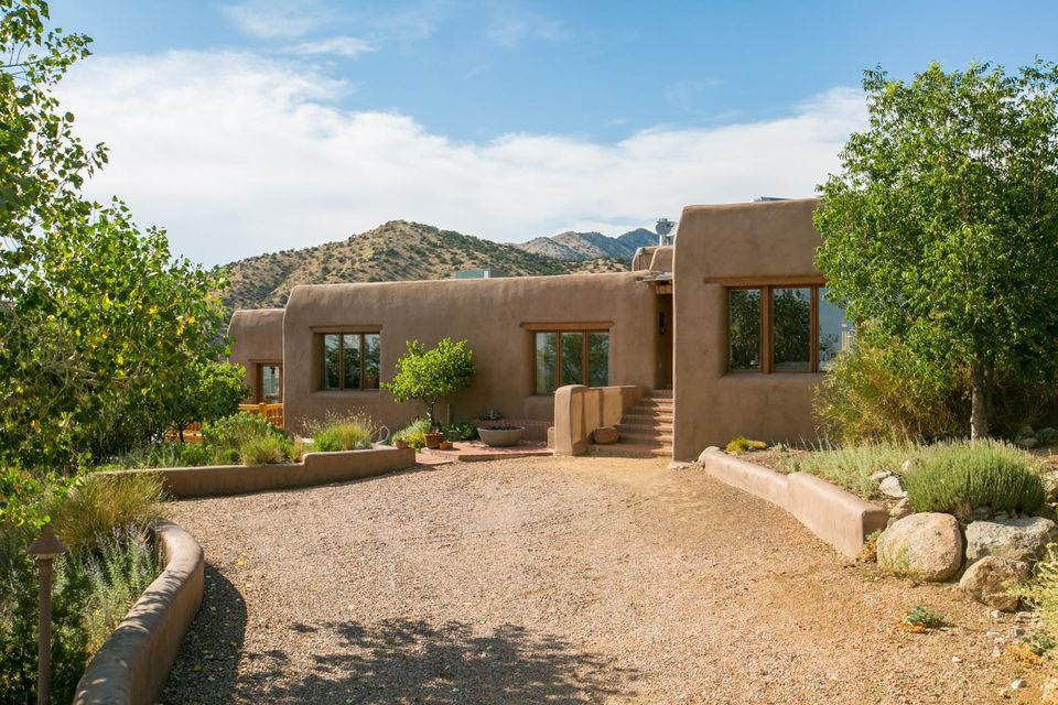 This classic Adobe, built by the acclaimed David Peterson is your quintessential Northern New Mexico home. Nestled in the foothills of the Sandias, the panoramic views are stunning. The home greats you with the finest touches. Solid wood gates and doors hand made by the builder are the perfect accent to the brick floors.  The home is equipped with a passive solar design as well as radiant heat for absolute comfort. The bedrooms boast closets all designed by California Closets, to maximize the space.  The open concept chefs Kitchen is perfect for entertaining family and friends.  Truly a one of a kind home