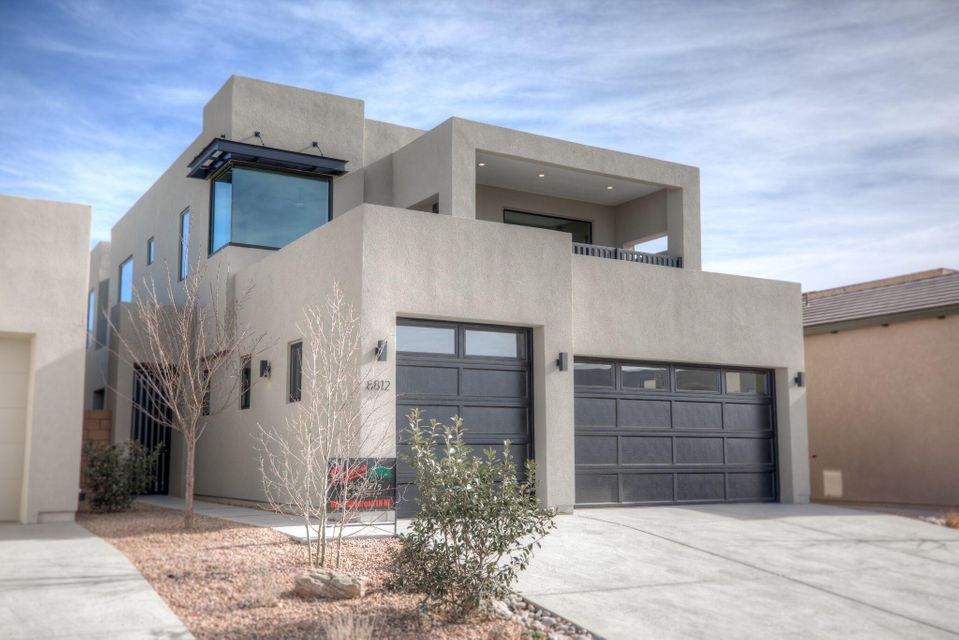 Stunning contemporary work of art built by Picasso builders, located in North ABQ Acres' newest gated community! Home features 3,377sf w/ 4 bedrooms, 3.5 baths, 2 living areas, a loft & a 4-car garage! Meticulous detail in every aspect of this impeccable home! Gourmet kitchen w/ upgraded cabinetry & crown molding, granite countertops, backsplash, built-in double oven/microwave, 6 burner cooktop, under cab lighting, center island w/ seating area. Steal beam ceiling flows into the gorgeous living area with an exposed brick wall and floor to ceiling custom steel fireplace! 1st floor master suite w/ custom lighting & barn door leading you to a spa-like bath! Free standing tub, walk-in shower, his/hers sinks & walk-in closet! Upstairs loft w/ views! Balcony w/ westside sunsets & covered patio!