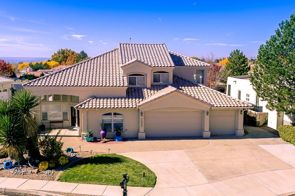 This elegant 2 story, 4 bedroom, 3 bath home located in the Northeast Heights boasts cathedral ceilings, a free flowing floorplan, and a breathtaking staircase. Enormous windows allow brilliant light in, creating a tranquil atmosphere. Relax by the fireplace in the large living room, or enjoy the adjacent kitchen with its ample cabinetry, massive island, and backyard views. The luxurious master suite includes a double sided fireplace, double sink, and spacious walk-in closet. Outside, brilliant flowers, luscious grass, and patio combination fill the backyard, creating a private oasis. Other features include a 3 car garage, phenomenal Sandia Mountain views, and a walled backyard.