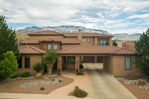 Custom elegance abounds in this beautiful Tuscan style home with views of the Sandia Mountains! Oversized lot, gated community, 4BDR/3 FULL BATH!Guest suite/office w/full bath on the main level.Two living areas plus loft.Custom finishes & fixtures throughout, new tile flooring, beam ceiling, REFRIG AIR.Gourmet kitchen featuring Subzero fridge, two ovens, gas cooktop, granite countertops,large island & bkfst nook and walk-in pantry.Private master suite features a double headed shower, jetted tub, gas fireplace, views, his & her vanities. Secondary bdrms have Jack-N-Jill bath & balcony!Private backyard has a covered patio, lush grass, waterfall, trees, shrubs and VIEWS!2CG with bonus 3rd bay for storage and carport!!  Desirable neighborhood of Estates at Desert Ridge Trails.