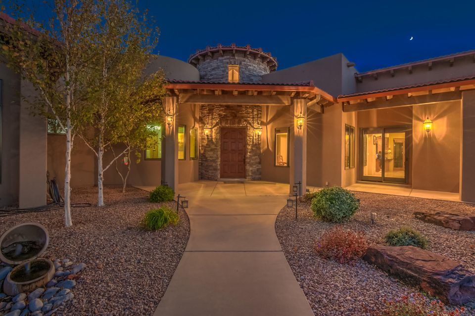 Location Location Location!! You will fall in love with this gorgeous single level Tuscan style home designed and built by Integrity homes, un-belivable quality and finishing touches.  Beautifully privately gated home in the highly desirable La Cueva Estates. Nestled on one of Albuquerque's premier streets close to open space for sensational  unobstructed views of both the sparkling city lights, warm, glowing sunsets and the watermelon Sandia mountains.  Located on a 1.47 acre lot with gated access from both Elena and Venice.  Oversized 4 car finished garage plus lots of parking, Entertainer's dream home. Open concept living with 12-24 foot high ceilings,. Impressive dining room with the large SCHONBEK chandelier with SWAROVSKI crystals and 2 sparkling crystal balls.  Gourmet kitchen.