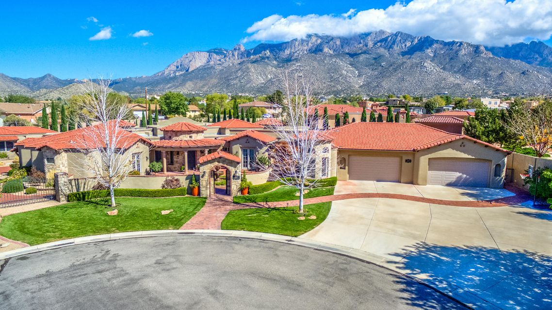 This exquisite 6 bedroom estate sits on 3/4 acres in a cul de sac in highly coveted Primrose Pointe. A serene brick courtyard with lovely fountain welcomes you and makes a statement at the entrance. The main living area has raised beam T&G ceilings, gas fireplace, and stunning views of the nearby Sandia mountains. The kitchen has raised, barrel rolled brick ceilings above rich dark cabinets and gorgeous granite counters. Appliances are Subzero-Wolf. The formal dining room is pure elegance, highlighted with a beautiful chandelier. The master suite is a peaceful and luxurious retreat with soaring ceilings, private French doors to one of the many patios, and a sitting area full of natural light and relaxing views, perfect for cozying up next to the gas fireplace and reading your favorite...
