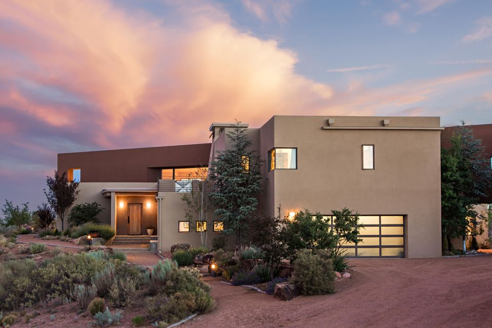 This dynamic contemporary home is defined by enchanting vistas, luxurious finishes, striking architecture, and amazing light. Enjoy million dollar views of multiple mountain ranges, the city lights, and the high desert landscape. Green built of ICF construction, this home features the highest quality finishes and energy efficient features. The kitchen is beautifully appointed with Hanks House furniture grade cabinetry, wolf and sub zero appliance suite, and rich granite. An open floor plan creates great flow for entertaining, and an elevator affords easy access to each level. A self contained casita affords flexibility and includes a living area, bedroom, bath and kitchenette. The master suite also affords incredible views, a luxuriously appointed en-suite bath & a spacious walk in closet.