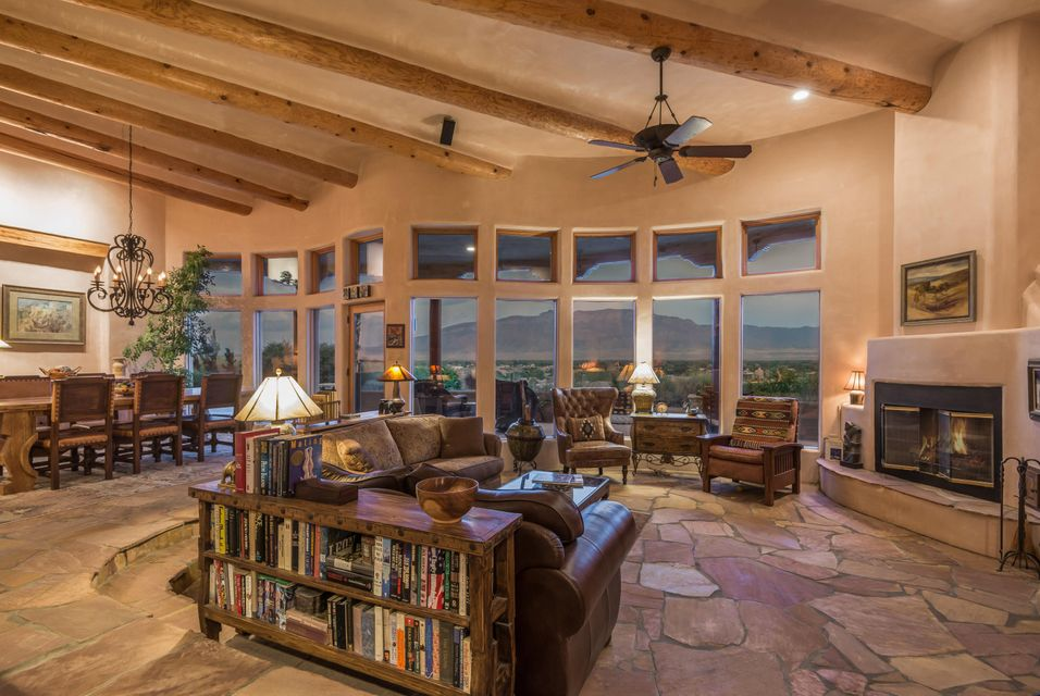 Imagine waking to sunrises over the Sandias, watching sunsets turn the mountains beautiful colors, and seeing the lights of the city sparkle from your home!  Eric Spurlock designed this custom split level home to capture the magic of living in NM.  Flagstone floors throughout, beautifully hand plastered walls, custom cabinetry and doors add to the beauty of this home. Large kitchen with island and leathered granite countertops provide ample space to be a chef and entertain at the same time.  Master suite has fireplace, views and a spa like bath.  Outdoor entertaining areas are spacious and covered with built in grill.  Rooftop spa with panoramic views.  New roof, new water heater, and solar power added,  See attached list for more updates.  Backyards fully fenced for pets.