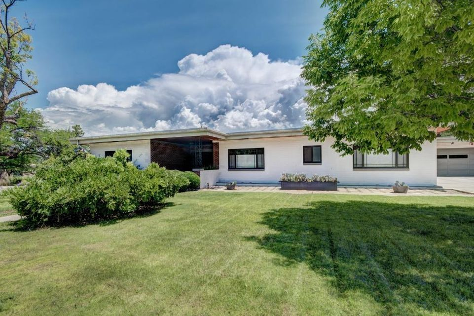 Take the 3-D Tour! Open House 1-3p Sun Aug 5th. Wonderful Parkland Hills home on a double lot has an impressive Mid-Century Modern profile. Enter from foyer into the grand, flowing & gracious living, family & formal dining rooms with views from massive picture windows. The privately tucked-away Master suite includes a daylighted walk-in & north-facing courtyard surrounded by rose bushes; 3 other generous-sized bedrooms. Huge eat-in kitchen has picture windows facing the Sandia Mtns--check out cool marble-brick backsplash between Jenn-Air appliances. Also: 2nd living area + bonus studio/office/5th bedroom sits just beyond. Whew..now come out back: stunning greenspaces amid 3 covered & open patios, creating numerous shaded sitting & play spaces. So much more to fall in love with--come see!