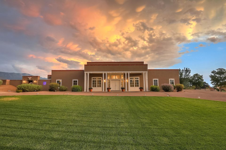 Gracious, Territorial Style home designed by Claudio Vigil is ready for multi-generational living. One level home with guest house provides room for all. Very light and bright with large rooms and open floor plan. Radiant heat and refrigerated air. Master is separated from other 3 bedrooms and provides a refuge complete with fireplace, luxurious master bath , attached exercise room or study, and door to the beautiful courtyard. Back courtyard has spectacular view of the Sandias. The guesthouse is self contained with kitchenette, bath, bedroom, and spacious living room with views perfect for in-laws or teens. The 4 car garage offers space for storage and multiple cars. Privacy abounds in this home, make it your own!