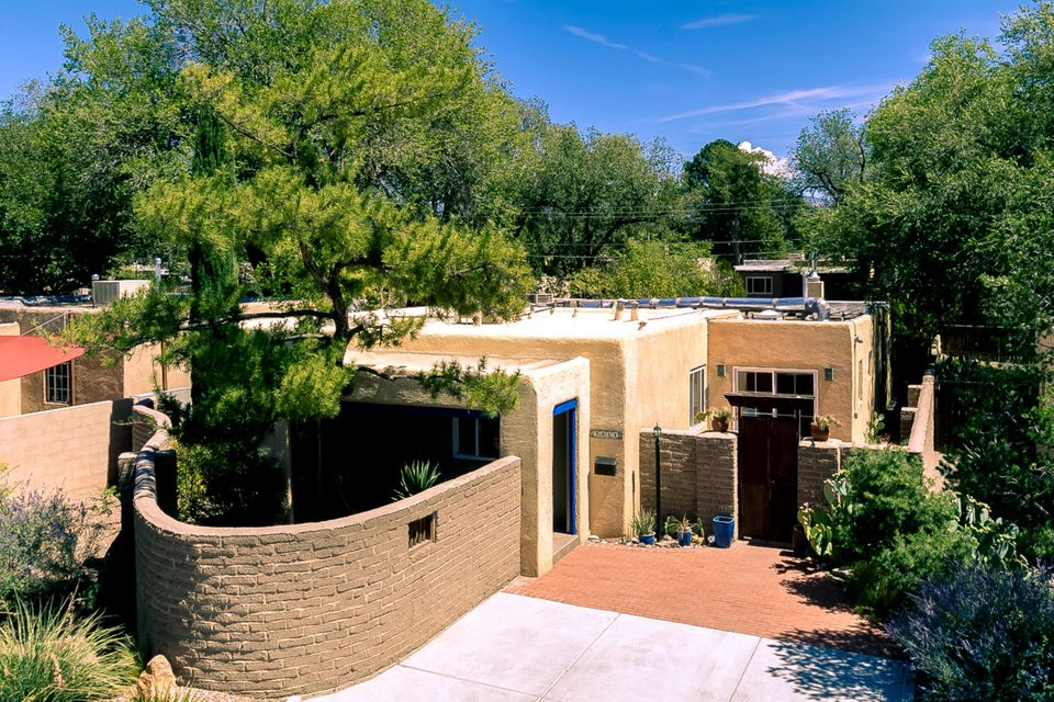 Nob Hill! Nestled in the heart of Monte Vista Historic District, this 2212 sq ft Pueblo-style, 3 bd, 2 ba sunlit casa is both Albuquerque-quaint & traditional, yet thoughtfully updated, surprisingly open & contemporary. Eminently livable as a whole, the home could also easily function as 2 entirely independent living spaces. Gourmet, high-end custom kitchen. Floors of oak hardwood, herringbone brick, premium tile. Modern, spacious, expansive great room. Master suite w/ charming fireplace discretely unconnected from bdrms 2 & 3.  3 private, peaceful outdoor patios. Elegantly rendered low maintenance landscaping. Approx $55,000 in upgrades w/in the last 3 years including 2018 graded TPO roof front of house. Sophisticated, comfy, understated, refined. W/in blocks of dining, shopping, & UNM.