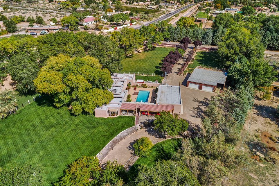 Incredible price for this graceful hacienda on almost 2.5 lush acres w/ mature cottonwood trees, flowing gardens, acequia rights, 8-car garage, 5-stall barn, stable & gorgeous pool surrounded by roses. Property boasts an oasis-like setting on the south end of Corrales, close to all amenities & yet a world apart. Santa Fe-style adobe home is full of character w/ viga & latilla ceilings, brick & wide-plank pine floors. Recent updates include new roof (2016), re-surfaced pool & deck, 2 new HVAC units & 2 new septic systems. Private setting close to walking/horse trails in a property ideal for entertaining or enjoying your animals. Wonderful horse property w/ pasture & turn-outs. Corrales country living at its very best!