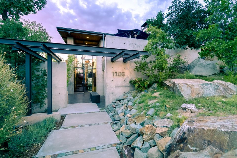 This centrally located award-winning contemporary architectural jewel boasts mountain, city and sunset views that make this splendidly open yet remarkably private home a zenith of modern urban living. Poured concrete construction, window walls, exposed steel beams, soaring ceilings, paneled walls, and clean lines make a dramatic statement, yet the design evokes comfortable ambiance and effortless indoor/outdoor living. At its hub is a generous greatroom and kitchen with access to a south-facing patio and a romantic ''martini deck''. A library/den, 3 bedrooms, 2.5 baths, private study nook, service room, and an oversized 2 car garage are surrounded by a rugged natural landscape. Life never looked as good as it does from 1105 Marquette Place NE.