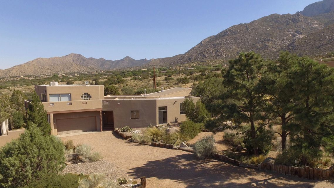 This custom home has it all - city & mountain views, backs open space (Sandia Mountain Wilderness), .64 acre lot and it's been beautifully remodeled. Big open kitchen w/ breakfast nook, granite countertops & stainless appliances. Sitting area off the living room has a copper fireplace and striking views. Master suite and 2 bedrooms are downstairs and the 4th bedroom is privately situated upstairs with a full bath, walk-in closet, fireplace, balcony and more views!! Other features include refrigerated AC, new roof, wet bar, built-ins and more! Located on a circle, the neighborhood is quiet with minimal traffic. Minutes from shopping, schools and major access routes. This unique indoor/outdoor dynamic assures gracious living year-round. Hiking & biking trails