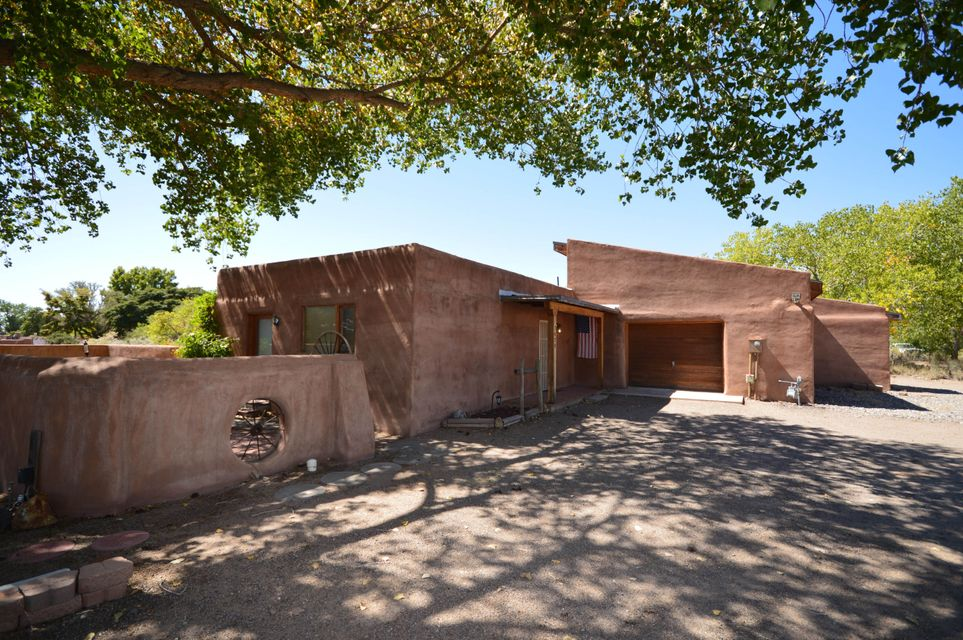 Located on a 1 acre corner lot on a quiet cul-de-sac in the south valley, this classic adobe home has exposed adobe interior walls and wood ceiling with beams throughout. Country kitchen has lots of cabinets and counter spacious plus large pantry. Two spacious bedrooms and two full baths. Oversized garage has large workshop area, and loft. Property is fully fenced with three gated entrances and two large storage sheds.