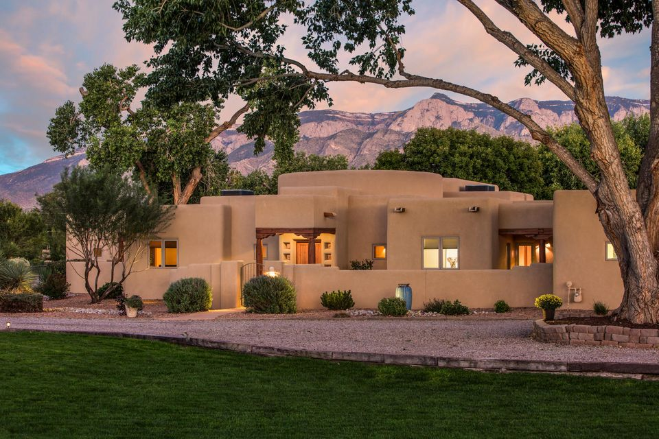 Luxurious and unpretentious. This 1.4 acre, green valley property is fixed in a private cul de sac just off Corrales Rd. Centuries old cottonwoods, courtyards, patios, lush lawns, and grand views of  the Sandias adorn the property. This 3000+ sq ft home features immense windows, open space, and an open sky courtyard fit for star gazing and morning yoga. The chef's kitchen accommodates quiet morning coffee and large gatherings, alike. This Sun Mountain custom home features energy efficient materials, radiant heat, on demand hot water heater, and stunning Saltillo tile and hardwood flooring. No detail was overlooked, and every inch of this home has been impeccably maintained. Your guests will take refuge here as they sit cozily on their private patio. Come experience Autumn Lane!