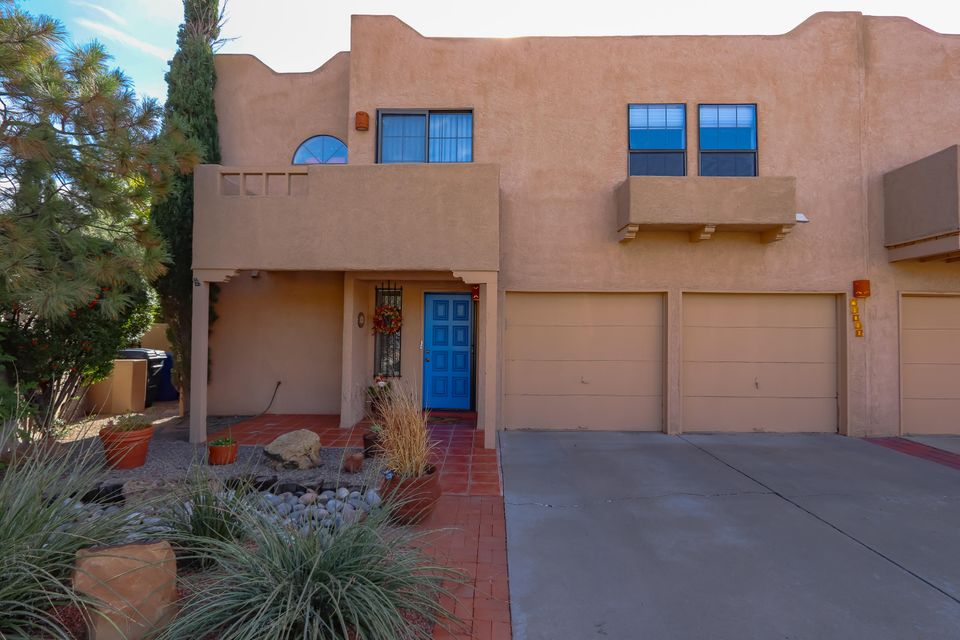 Absolutely Gorgeous!! Must see this Stunning 2 story Pueblo Style Townhome in the UNM area! Featuring a large great room with gas log fireplace & raised ceilings, kitchen w/brk bar, stainless steel appliances, enclosed Sun Room just off of the MB, double MB sinks, walk in closet plus Loft For Study/Office area .Refrigerated air. Attached 2 car garage.  Wonderful walled backyard with grass, nice covered patio area & storage shed. No HOA.