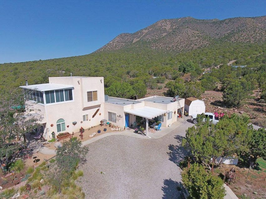 Want Views?  You can't get any better in the entire East Mtn Area!!  Beautiful Custom Home sits at the base of South Mountain and is at the end of a road, very quiet and secluded.  Lots of Trees, has Shop with 220 power, 3 storage sheds, fenced back yard for dogs, 2 car carport, 24'x36' Horse Barn with 2 Stalls w/pipe runs, wash rack, hay storage area, Tack room, Elec, Water, Pasture fenced for horses.  Very unique home with in laws quarters, home has two masters, two kitchens, the Upstairs Master has sitting room, Sunroom Sleeping area with Forever Views.  Living area has gorgeous beam ceiling. Home has Cozy Wood burning and pellet stoves. Heated Garage. Won't last long, Come see me today!