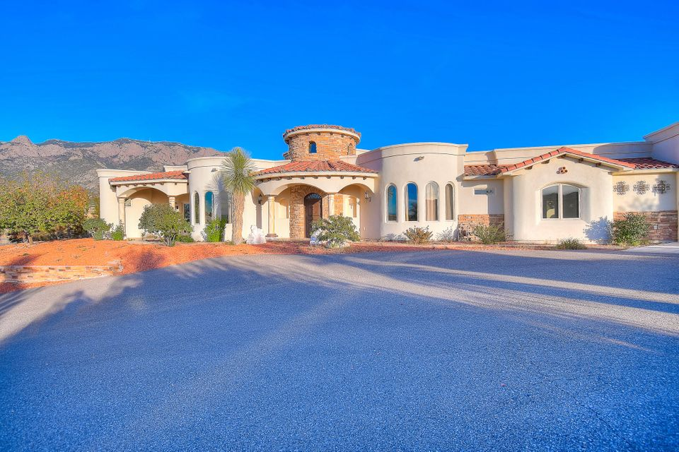 Take a walk through this exquisite custom Mediterranean Style Home! Breathtaking views from every angle, whether it be city lights or the majestic Sandia Mountains. Gourmet Style kitchen accompanied by Viking appliances, Knotty alder custom cabinetry, matched with elegant granite countertops. The Owners Suite has a custom kitchenette, two way fireplace, private pool access, double walk-in closets and a second laundry location.  Master bathroom has a massive walk-in shower with 10 water locations, rain shower head and beautifully decorated tub with imported stone from Spain. Exterior includes an amazing outdoor kitchen with 20x40 custom pool, perfect for entertaining! Drive through garages that open on both sides.