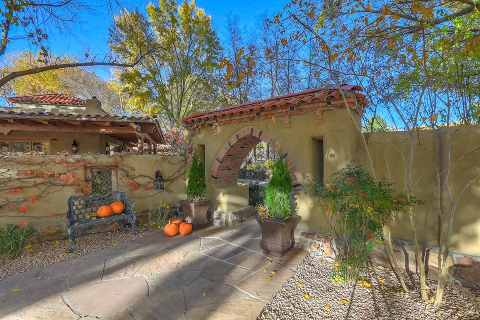 Breathtaking! Coveted Eakes Rd/Los Poblanos area of Los Ranchos. Charming, elegant, 4-5 bedroom adobe home designed by John Calvin.  Situated on 2.4acre landscaped estate lot backing to bosque & trails of the Rio Grande, this home & guest house provide the ultimate in privacy & verdant beauty of the North Valley.  A beautiful brick barrel vaulted entryway welcomes you to this warm & inviting home.  Flagstone floors throughout living areas, intricately carved beams, & doors add to the Moorish/New Mexican design of the home.  Updated kitchen with granite & high end appliances. Master bath with marble, granite & travertine evoke Roman bath.  Portals, fireplaces, water features, gardens combine styles of traditional New Mexico & classic Spain.  Refreshing pool, spa; adjacent guesthouse/cabana!