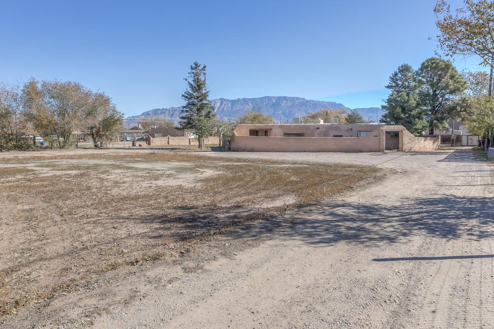 Set back off 4th and off the beaten path, on a private road, close to amenities and views of balloons flying from Balloon Fiesta Park. Skip the rush hour commute across the River - Settle in the Far North Valley! All Adobe home w/ a rubber membrane flat roof featuring Brick and Saltillo floors, latilla and tongue and groove ceilings, and Multiple Living Areas. This original single family home has been used as a duplex so some remodel may be desired to remove one kitchen and return it to a single family residence and it is priced accordingly. Outside there's nearly 1 full irrigated acre to hang out with your horses, relax in your landscaped courtyard, or just to have a little space between you and the neighbors. Close to Raymond G Sanchez Community Center and Alameda Elementary. Won't last!