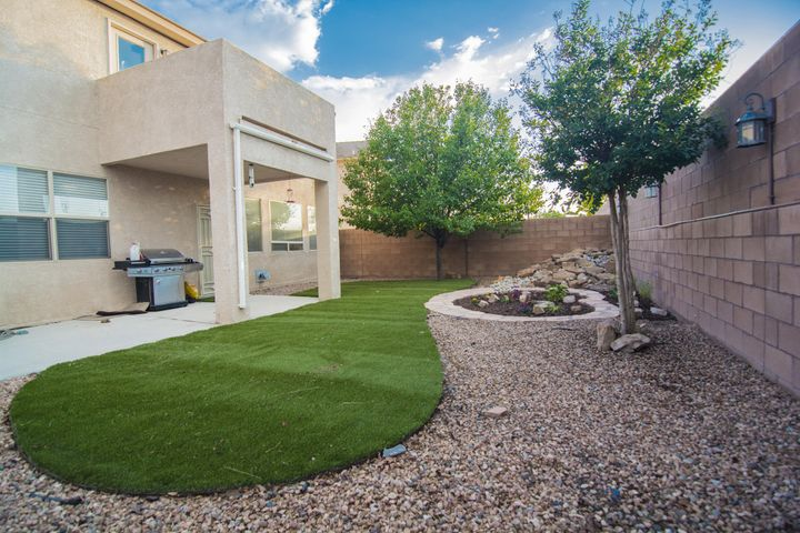 Landscaped backyard with covered patio and exterior lighting.