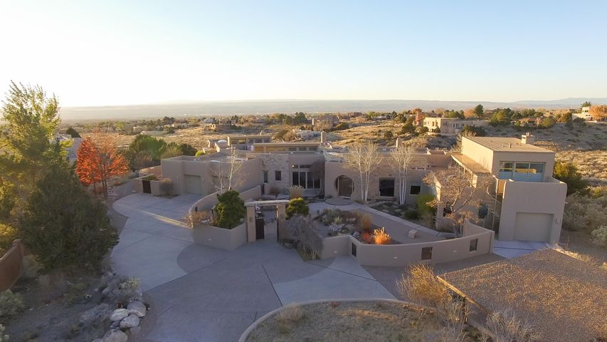 When our most outstanding construction professionals, Richard Schalk, John Blueher, and Alana Markle have created a wonderful piece of art on a dramatic site, it is hard to find any competition. Featured in Su Casa, this home has now become available with well planned gardens on every side, mature landscaping and a studio/office addition which features magnificent Sandia views.  Immaculate and elegant, dramatic front door and entry gates, travertine floors, gourmet kitchen and luxurious main floor master suite with marble vanities and tub. Elevator insures no steps anywhere.  Views from every direction, built with uncompromised sight lines so the views parallel the occupied areas of the house. This masterpiece could not be replaced for the current price. Show to your most particular client