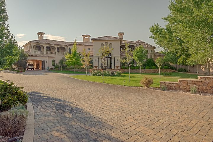 Exceptional estate property with incredible details rarely found in Albuquerque area homes. Versaille travertine, hardwood floors and plaster walls create a sense of luxury as you enter through massive front doors. Cantera stone--fireplaces,crown molding, window and door surrounds throughout reflect the exquisite taste of the owners who created this masterpiece for their family. Massive handmade arched metal French doors and railings, marble and stone sinks and counters, tasteful custom kitchen w/Wolf and Subzero make it also feel like home. A resort-like atmosphere is found in the outdoor family room and kitchen adjacent to the pool. An elevator easily accesses upstairs spaces including a family area with fantastic mountain views, a balcony, a dance floor sitting area and guest wing.