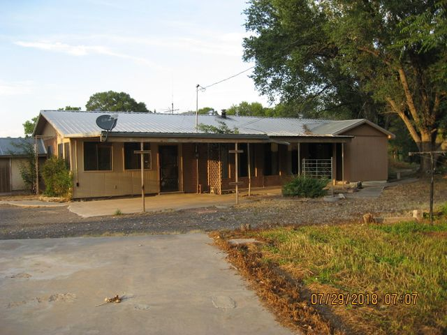 This property is located on over 6 total acres of agricultural land with irrigation recently laser leveled. Several outbuildings with several pipe fenced corrals. The home has 3 bedrooms, 3 bathrooms, metal roof and fairly new furnace. Two of the bedrooms have their own full baths.  Large front enclosed patio room (15.5'x9.5', 147sf) not included in square footage. Come bring your horses and other livestock and enjoy the quiet setting this property offers back off Camino De Los Chavez and adjacent the irrigation ditch.  This property has great potential.