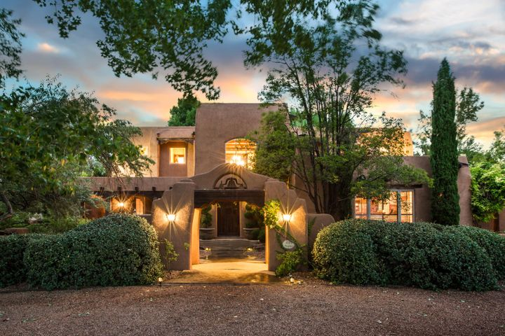 Stunning Santa Fe Style adobe in a park like setting on 1.1 acres in Tinnin Farms,Los Ranchos de ABQ!The two story grand adobe foyer sets the stage for this dramatic entry into a home with corbels & beams & classic SW architectural detailing. Beautiful metal clad wood windows & stained concrete floors. Elegant living room with kiva fireplace opening to large wrap around entertaining portal. Formal dining room with seating for 10  overlooks the portal and lush backyard. Large gourmet kitchen with 8 burner wolf cook top, 2 new built-in ovens and large granite bar and sub zero. Relax in the library just off the kitchen and breakfast nook with kiva fireplace.The spacious gathering room is perfect for those Sunday afternoon football games - lounging in front of the fire w/family and friends.