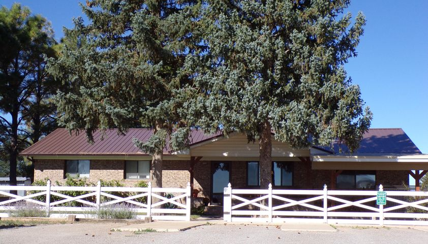 This Moriarty, New Mexico horse property has it all featuring a 4-stall insulated barn with a roll-up door, 150'x300' ropin' arena currently planted in winter wheat, catch pens off the arena and a multitude of  other pens, many frost free hydrants, 60'x40' shop with power, heat, air conditioning, mezzanine storage, and office area. Not to be missed is the large equipment storage area with a concrete loading dock. This is a lovely ranch style home with 4 bedrooms, 3 bathrooms, stunning kitchen, large great room with a wet bar and new vinyl laminate flooring. Beautiful heated sun room and hot tub. The master suite has an updated bath also with new flooring. There is an area off the bedroom that can be used as an office or reading room.  This home is made for entertaining especially