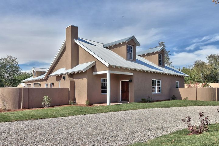 GREAT NEW PRICE! 58K REDUCTION on this rarely available,  NEW construction on Rio Grande Blvd. in the sought after North Valley! Two story Northern New Mexico style with 3 bedrooms ( all en suite) plus office, 3.5 baths, beam ceilings, Sierra Pacific windows, brick and wood floors, high end Kitchen Aid appliances and dining bar. Master bedroom and separate office on main floor. Finished, bonus room (aprox 215 sq ft)  for walk-in storage. Fully landscaped .33 acre lot includes new, 10k private irrigation well, professionally planted trees & full sprinklers. Covered patio is perfect for entertaining. Oversize garage has two 8 ft overhead doors to accommodate large vehicles.