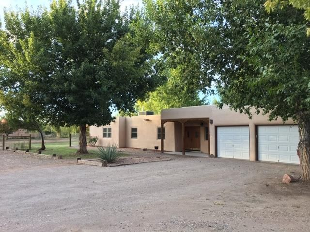 Terrific Corrales location for this charming Pueblo Style home. Situated on one irrigated acre with plenty of room for your animals. Mature trees and irrigation water is available. Fabulously remodeled kitchen with granite counter tops, pantry, gas stove, bar, breakfast nook. Open floor plan with two living areas, wood-beamed ceilings, and a two-way adobe fireplace. Two master suites. One has a Kiva fireplace and private patio. Second is perfect for guests/in-laws. Close to many restaurants, shops, and Corrales Elementary School. Covered back patio is a perfect entertainment spot. Back yard access. Great, well-kept neighborhood that makes you want to move right in. Drop by and see your new home!