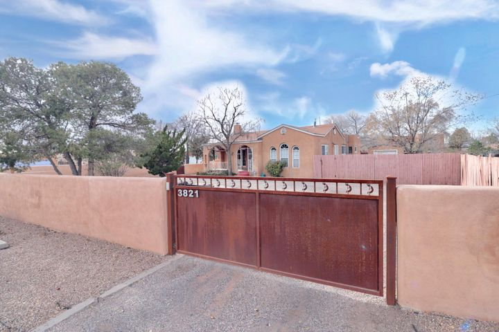 Perfect Home on a corner lot in the desirable North Valley. Historic Terrone Adobe built in the 1920's, converted to a duplex in the 1940's and now beautifully restored to a single family residence with all the charm you could think of. Original hardwood floors, arched doorways, updated kitchen and bathrooms and a cozy fireplace to enjoy on those cold winter nights. Take time to enjoy the covered front porch, enclosed landscaped front courtyard with a nice water feature that conveys. Large corner lot with attached 1 car garage. Home has a basement for extra storage. Backyard access is an added bonus to this beautiful home. Call today for your private tour.