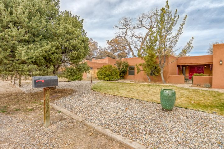 Beautiful adobe-style home with open, light, welcoming and flexible floor plan, backing up to the river with views of the bosque, all within the migratory bird flyway and hot air balloon box. 5 bedrooms, 3 baths & multiple living areas laid out to accommodate various configurations, including two Master suites, in-law wing and a detached casita/art studio space. Country living, with city shopping, dining, entertainment, farmers markets, Villages of Los Ranchos and Corrales all less than 10 minutes by car, bicycle or pedestrian/equestrian trails. Quiet, upscale, secluded, horse-friendly location, this home is nestled in the back of the neighborhood with gated access to the bosque and bridle trails. Heavily treed, landscaped one+acre lot with many fruit trees, grapes & mature cottonwoods