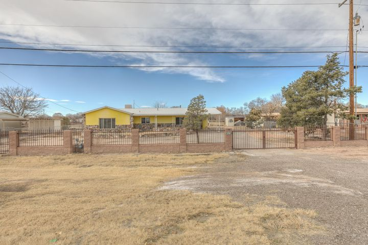 This listing represents details for 2 homes. The main home - 3 beds, 2 baths, 2413 SQFT fireplace, large living area and a den. Guest house or mother in law suite - 3 beds, 2 baths, 1349 SQFT, 2 sheds/workshops. Its situated on 5.24 acres in the heart of Los Chavez. There is a 50x40 FT shop and extra shed and both include 220 Outlets on a concrete slab. Total of 2 carports, and plenty of garage space. Large RV/boat/trailer carports attached. Concrete ditch irrigation. With some TLC and new carpets these homes have some amazing potential! Don't miss this great opportunity!  Yamaha 4 wheeler, Travel Trailer, 16 ft flat bed, 10 ft flat bed, Bushhog Mower do not convey.