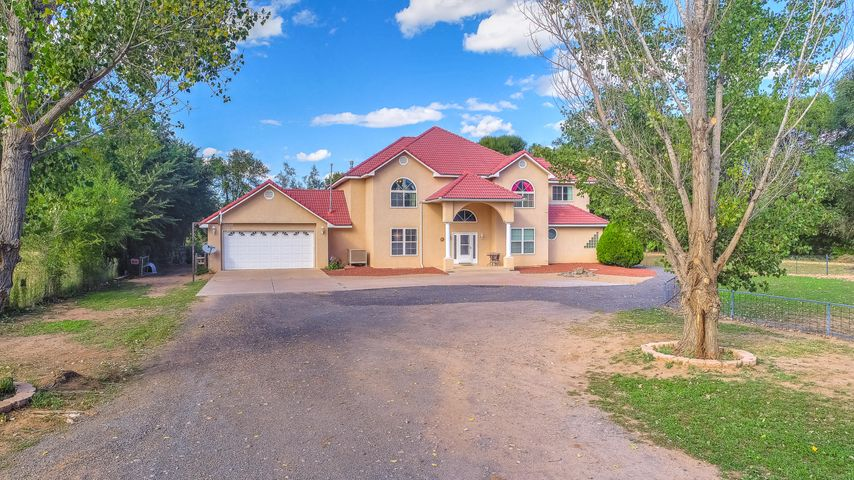 Very rare opportunity on iconic Tondre Road.  This sprawling estate is gated and features over 4,000 square feet of living area with 5 bedrooms plus an office. The master suite is on the main level & features a spacious bath with separate shower & soaking tub along with an ample closet.  The grand curved staircase leads to four bedrooms & two full baths on the upper level. Formal dining room, separate workout room or office. The living room boasts soaring ceilings and a fireplace. The gourmet kitchen is complete with granite countertops, stainless appliances and a cooktop in the island. Relax in your screened-in porch overlooking your private lawn. Ideal location for privacy and yet just minutes to main street and only 20 mins to ABQ. Come take a look today, you will not be disappointed!