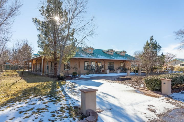 Savor this  serene and private location yet only minutes from the Bosque trails and conveniences such as shopping, entertainment, restaurants, and medical facilities.  Rocking-chair-ready porches beckon you to this beautiful, single-level,  Northern New Mexico hacienda that offers premium comfort with a dazzling array of amenities. High ceilings* 3 fireplaces* 2 living areas*formal dining plus a breakfast nook*all bedrooms have their own bathrooms*fabulous study with built-in bookcases and separate entrance*radiant heat* refrigerated air conditioning*a chef's delight kitchen...stainless steel, granite, ample counter/prep space*oversized 3-car garage perfect for storage & hobbies*lush, green yards, shrubs, plantings and trees on 1/2 acre lot.  Truly a refuge of joy and relaxation!