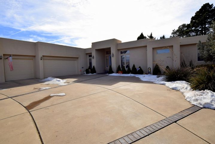Stunning custom SW contemporary in Siesta Hills.   Close to KAFB, VA Hosp, Sunport,  Nob Hill & UNM.  An entertainer's delight!  Open, flowing plan.   Impressive great room with soaring 14' ceiling.  Gourmet kitchen with built in sub-zero refrig, bkfst bar, & tons of quality cabinets.  Large semi-formal dining room + bkfst room.  Huge butler's pantry area.    Abundant windows bring in the natural light.   BR next to MBR ideal for office or nursery.  Guest BR with in-suite bath great for in-law or teen.   Massive circle drive leads to oversize 3 car finished  garage with laundry sink & storage galore.  REFRIG AIR.  Two HW heaters with fast hot water.   Big .39 acre lot with low maint landscaping & privacy.  Mature evergreens, fruit trees & roses.     RV access possible on E side of house.