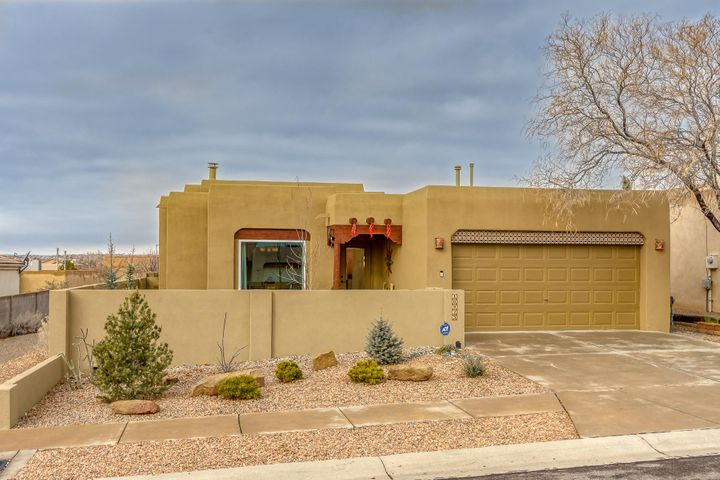 Start the New Year in this Southwest pueblo  charmer! . . Dramatic vigas span the greatroom ceilings. Warm up with the cozy Kiva fireplace in the spacious greatroom. Stainless appliances adorn the open kitchen with beautiful granite countertops and tile backsplash. Relax and unwind in the Master suite with a gas log fireplace, separate soaking tub, huge walk-in closet, double vanity, and much more. Recessed lighting, updated fixtures, skylights, and Plantation blinds throughout. New paint, gleaming wood floors, Beautiful low maintenance landscape. Experience the beautiful New Mexico Sunsets from the covered patio. All of this just minutes from great dining, shopping and entertainment