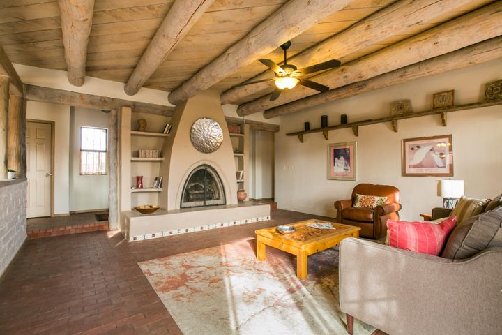 What an opportunity to own a North Valley adobe home!   So warm and charming.   Designed to be passive solar, south sun streams into your kitchen, dining, living room and master bedroom.   Beautiful SW features include brick floors, vigas, tongue and groove ceilings, exposed adobe, and kiva style fireplace.   Kitchen has island with breakfast bar and pantry.Generous master bedroom with patio doors to rear yard, walk-in closet and bath with double sinks.   Two nice additional bedrooms with a full hall bath.   South facing rear yard with winding paths, southwest plantings, gazebo and large shed.   This is a precious home .  Back on Market!  Buyer's financing fell through.   Inspections and repairs done!