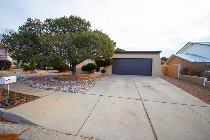 This lovely ranch style home has an amazing floor-plan. Bedrooms are located at one end of the home, with two large living areas and kitchen at the other.  Located on a cul-da-sac, with backyard access, over-sized carport, and a private walled courtyard. The Backyard offers great landscaping with a covered wooden patio, and a stuccoed shed with garage door to match.  Come enjoy the beautiful Sandia Mountain views at one of the most desirable locations in the city. Your new home awaits.