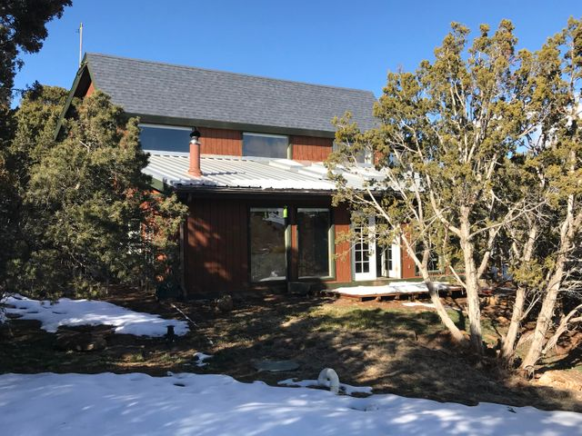 Bright, open mountain home on quiet cul-de-sac!. Spectacular views, passive solar, brick floors, decks, vinyl thermal windows, large garage and fenced backyard (and dogrun). Community water, Advanced Septic -new in '16, paved roads, central Cedar Crest location, community park, & access to 700 acre open space and trails nearby. Office-type room at top of stairs could easily be made a third bedroom. One bedroom on main level could be configured as a master en-suite. High-speed cable internet available.