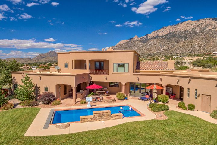 Custom TC home on spectacular Sandia Heights view lot.  Mountains and city vistas from everywhere inside and out.  Circle drive and two-2 car garages will fit your cars and large toys. Outside living area features auto covered pool with hot tub, outdoor kitchen and fire pit. 2018 TPO roof.  Refrigerated air (4 units) Interior features include diamond plaster walled entry, travertine flooring, triple pane Pella windows and more.Gorgeous well fixtured kitchen and pantry.  2 master suites w/ views, separated from guest or kid's wing.  One main level master suite (in-law suite) and second floor all master suite.  Guest or kid's wing has its own family room area with built in desks.  Original owner and beautifully maintained.  Move in ready for new buyer.