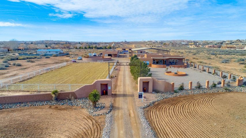 Turn-key and ready for accomplished horseman.  This horse training facility, conveniently located NW of Alb, & 45 minutes S of Santa Fe,  in Corrales, features 7 acres w/ fully equipped 11- stall barn w/off. &  apartment.10 runs w/cover, 7-stall foaling barn/shop, 80 X 150 covered arena, turnout, round pen, plenty of irrigated pasture! w/MRGCD. A fabulous custom home w/sep. casita,  2754 sf home features, 3 BR, 2.50 BA, 2 CG.  Well designed for spacious living. Beautiful tile floors, high ceilings w/vigas, kiva fireplace, windows that frame the mountains!  Cook's kitchen, island, custom cabinetry, nat'l gas stove, micro, dining, and unbelievable MBR suite.  FP, views, access to east portal.  2 BR, bath, & office w/sep courtyard entry.  Excellent opportunity for investor to subdivide in tim